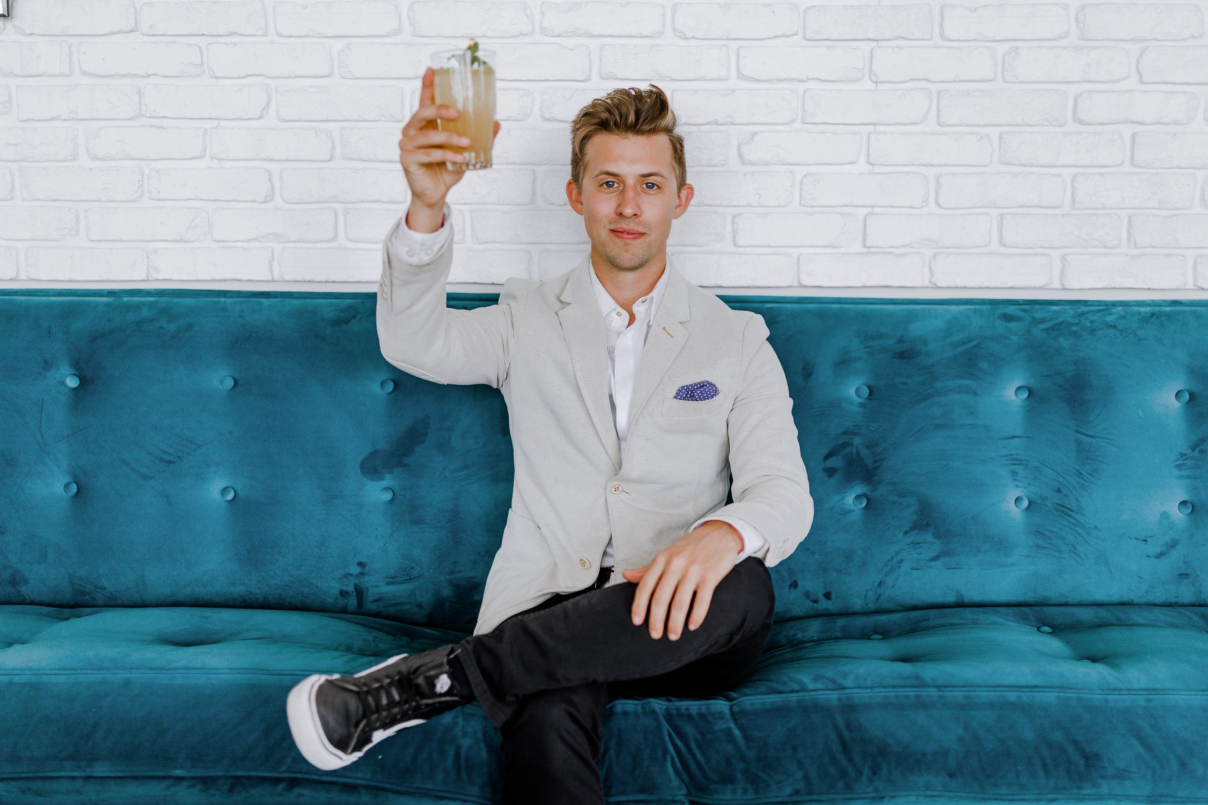 A man toasting himself alone on a couch