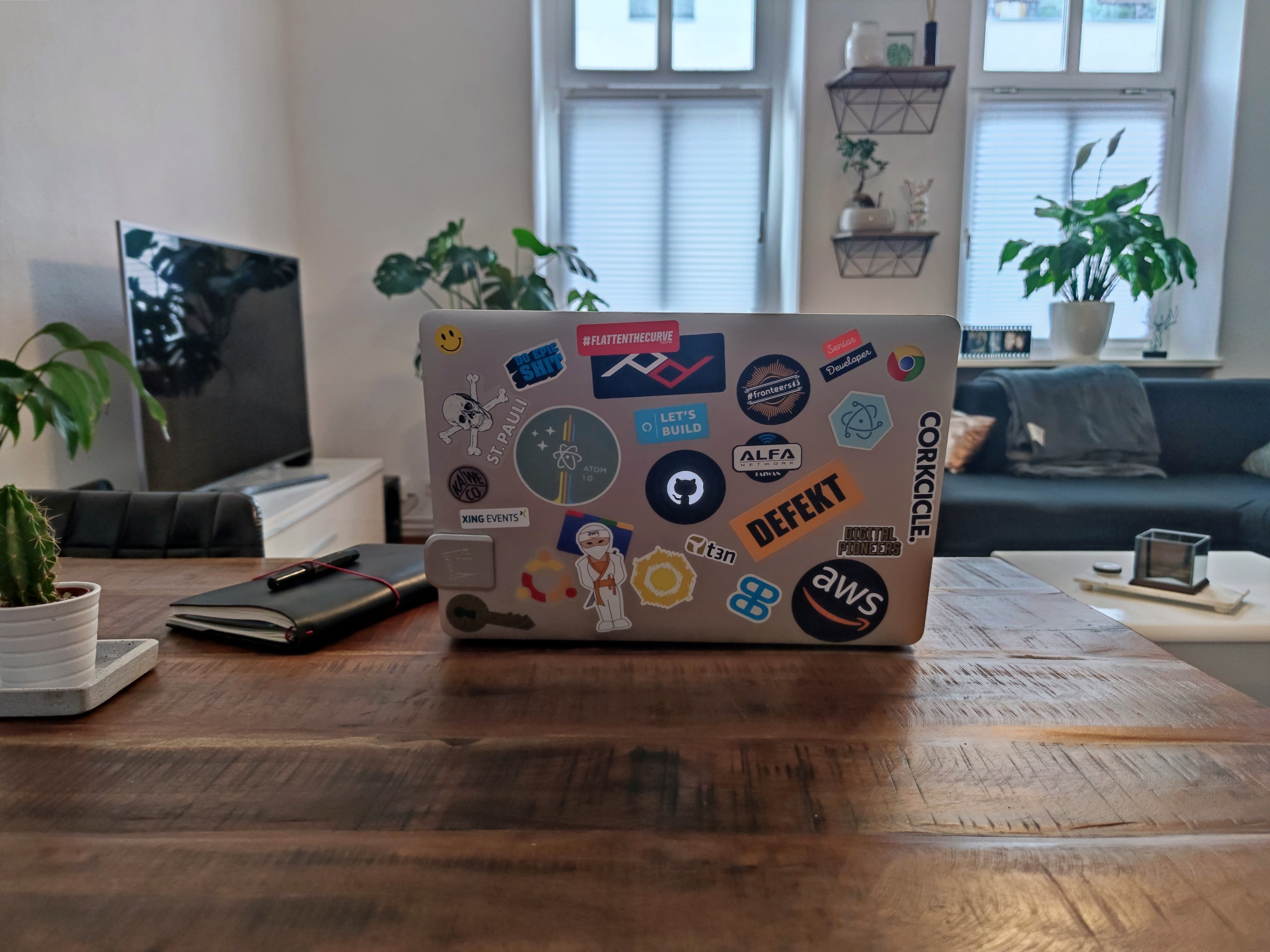 A MacBook with a bunch of stickers on it