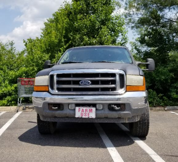 """Pickup truck without license plates, just """"Farm Use"""" on a cardboard plate"""