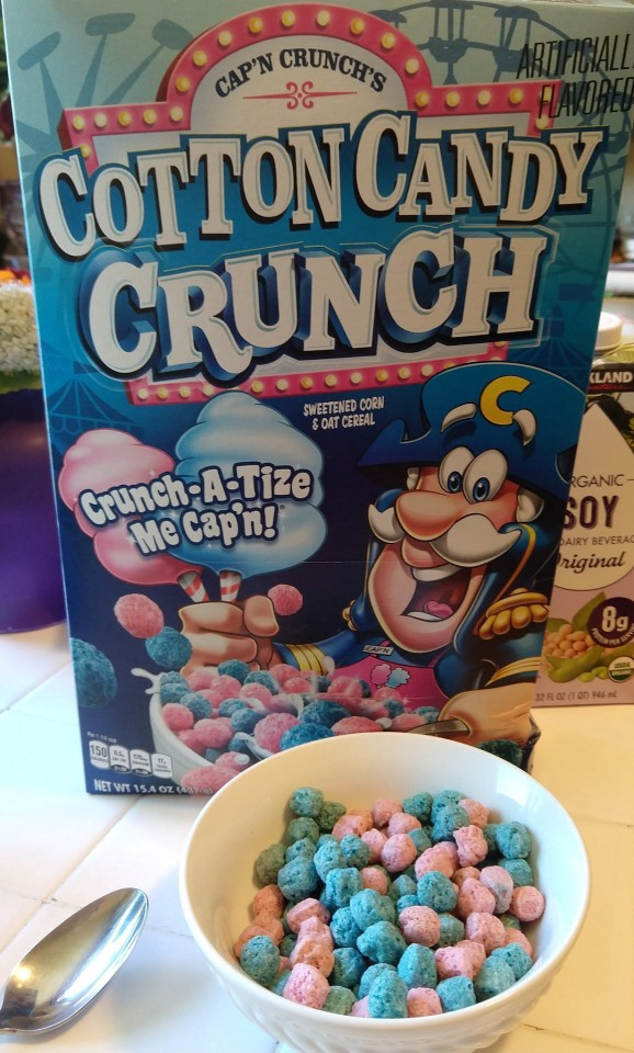 "a box of ""Captain Crunch Cotton Candy Crunch cereal"", with a bowl of the cereal in front of it. Both are blue and pink."
