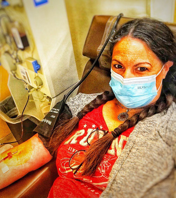Writer donating plasma. photo of them lying in a chair with a needle in their arm and you can already see the red blood being drawn