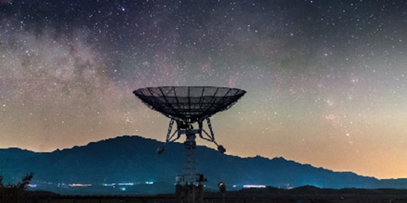 satellite dish with the silhouette of a mountain and a starry sky