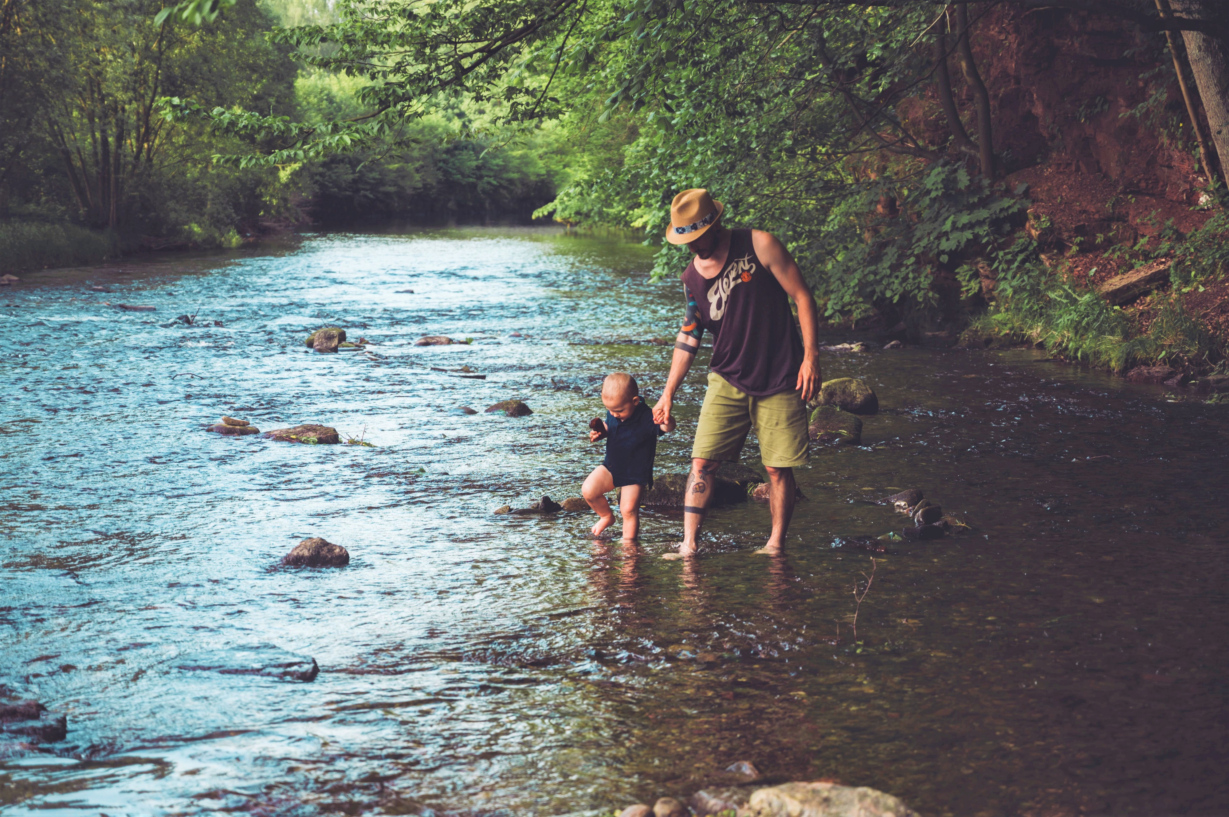 man wearing hat sleeveless shirt green shorts holding young child's hand walking through river in forest