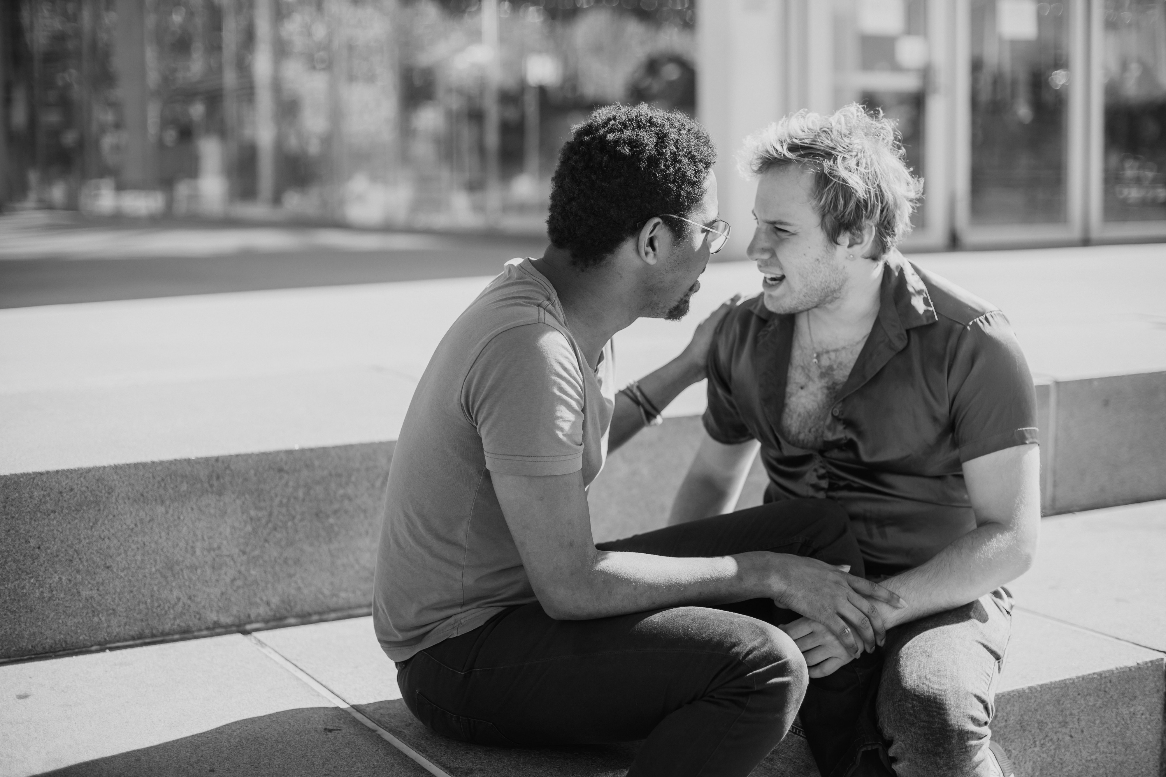 Two men sit outside on concrete steps. One gently touches the other on the arms as they appear to argue.