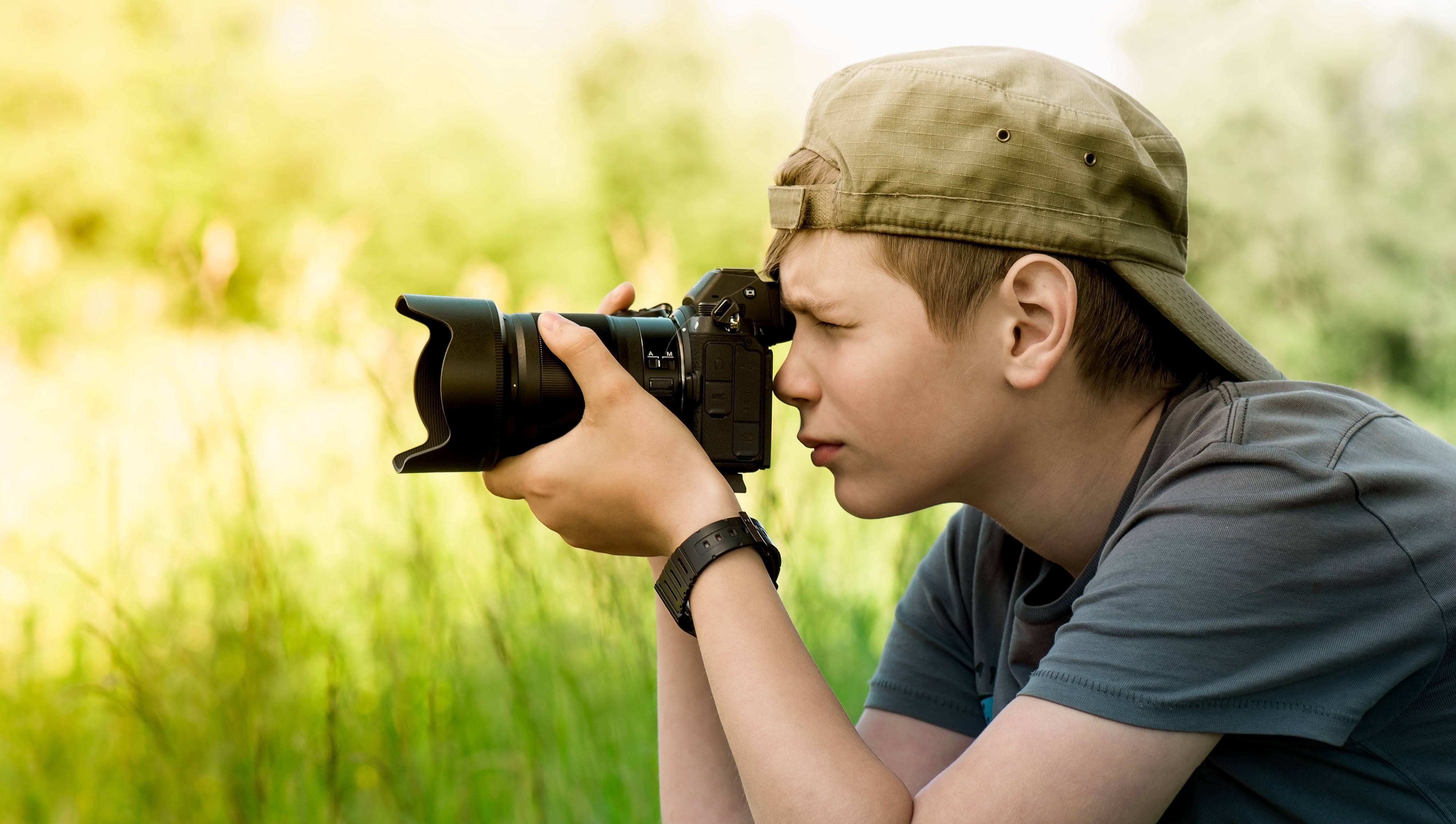 A young man takes photos in a meadow.