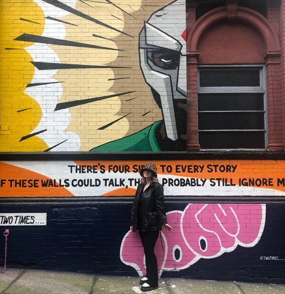 A student stands in front of a mural at Leeds' Belgrave Music Hall.