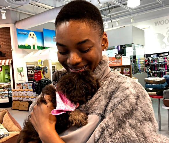 Author, black woman with short hair, holding small brown puppy with pink bandana in pet store