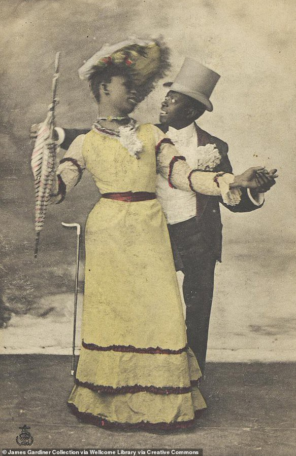 An antique photo showing two black performers, one dressed in a suit with a large white corsage, the other dressed in a yellow dress with red ribbon and holding an umbrella.