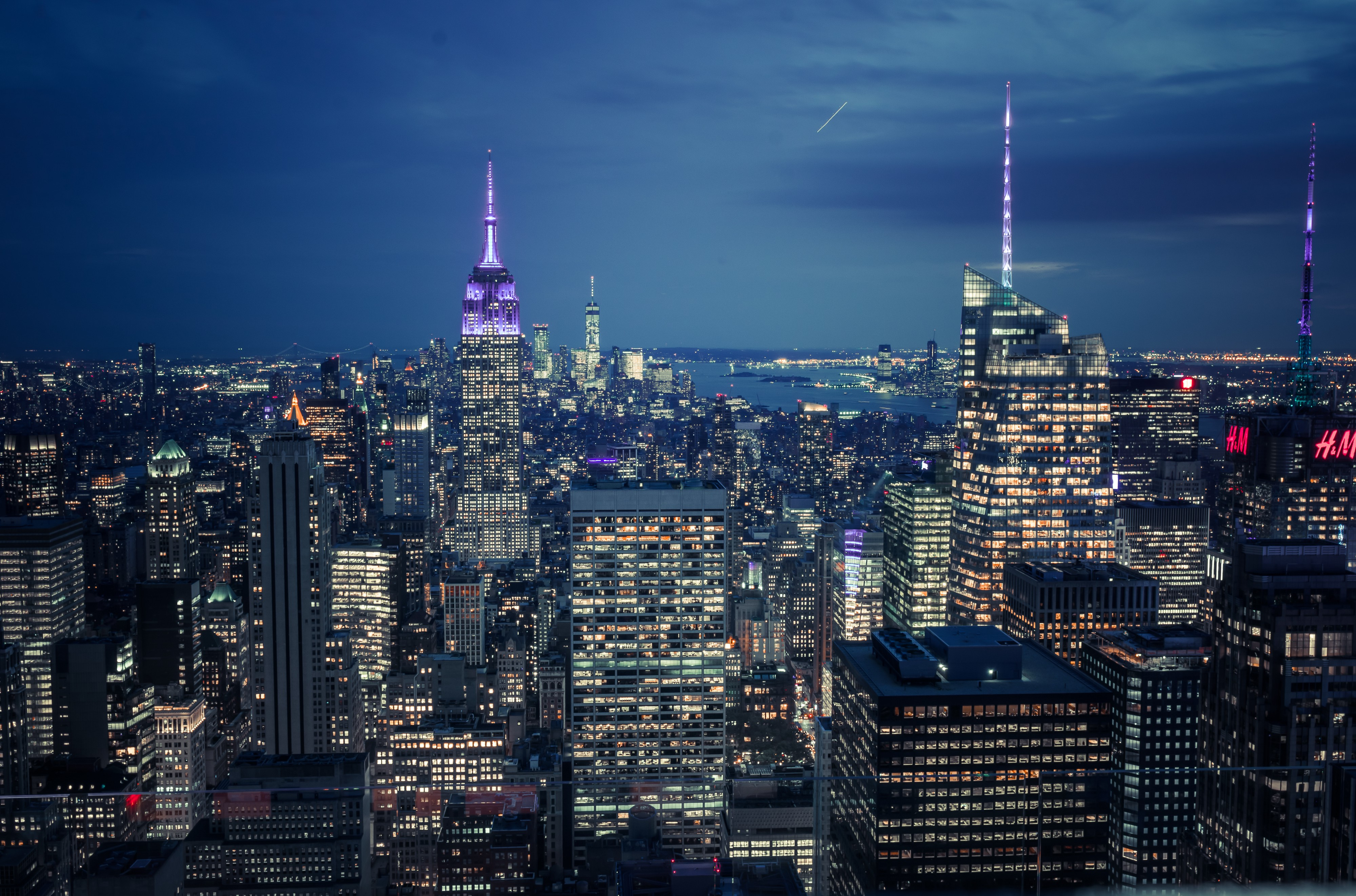The New York skyline in the evening with lights in the windows of buildings against a darkening sky.