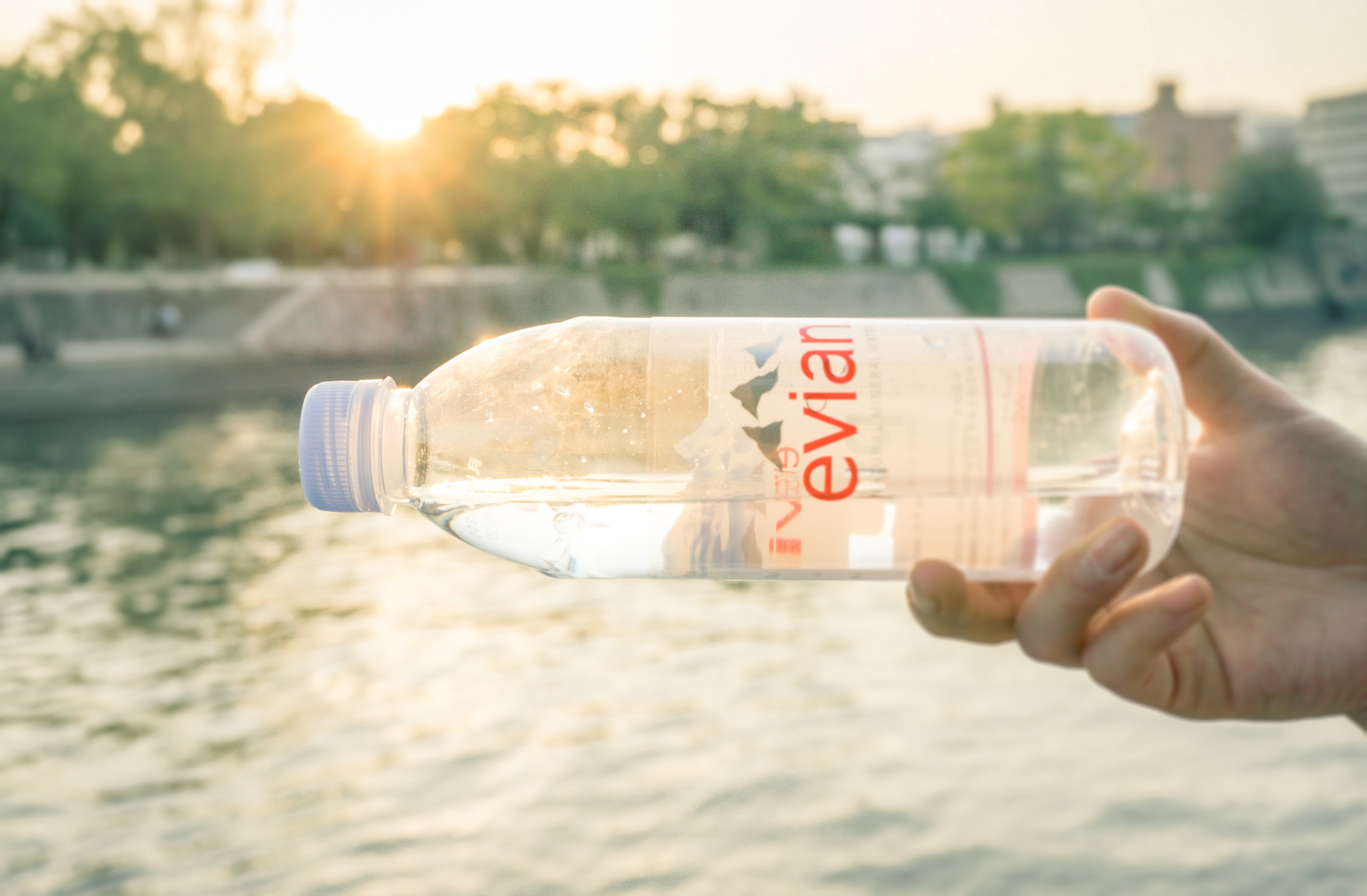 A person holding a bottle of Evian water.