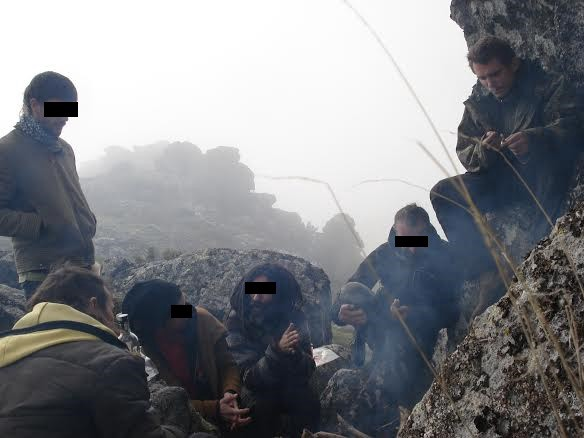 A group of people discussing anarcho-primitivism in rocky mountains nature, in fog. They have blackened faces to protect their identity.