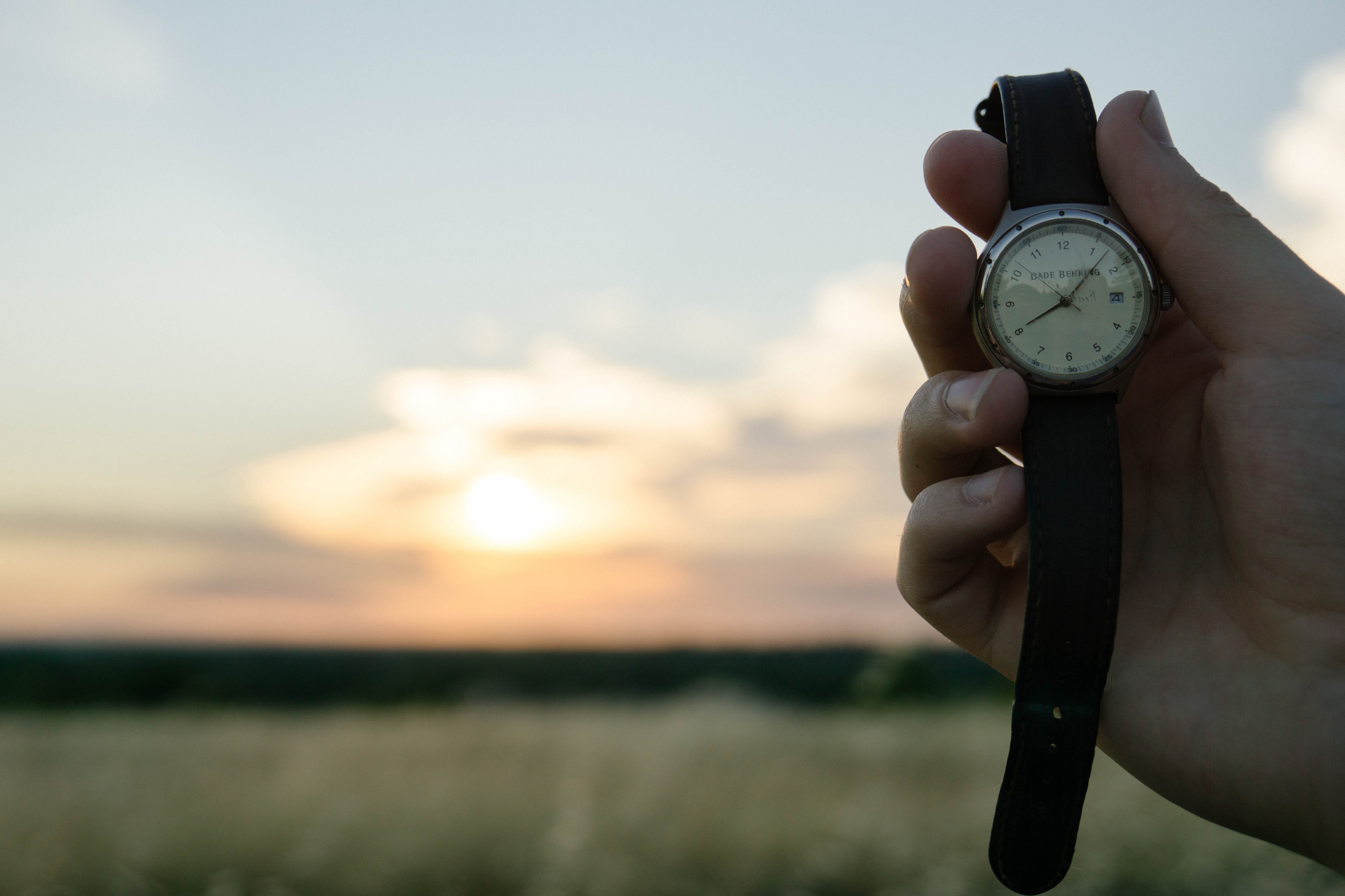 A hand holding a pocket watch, and the sun setting in the background.