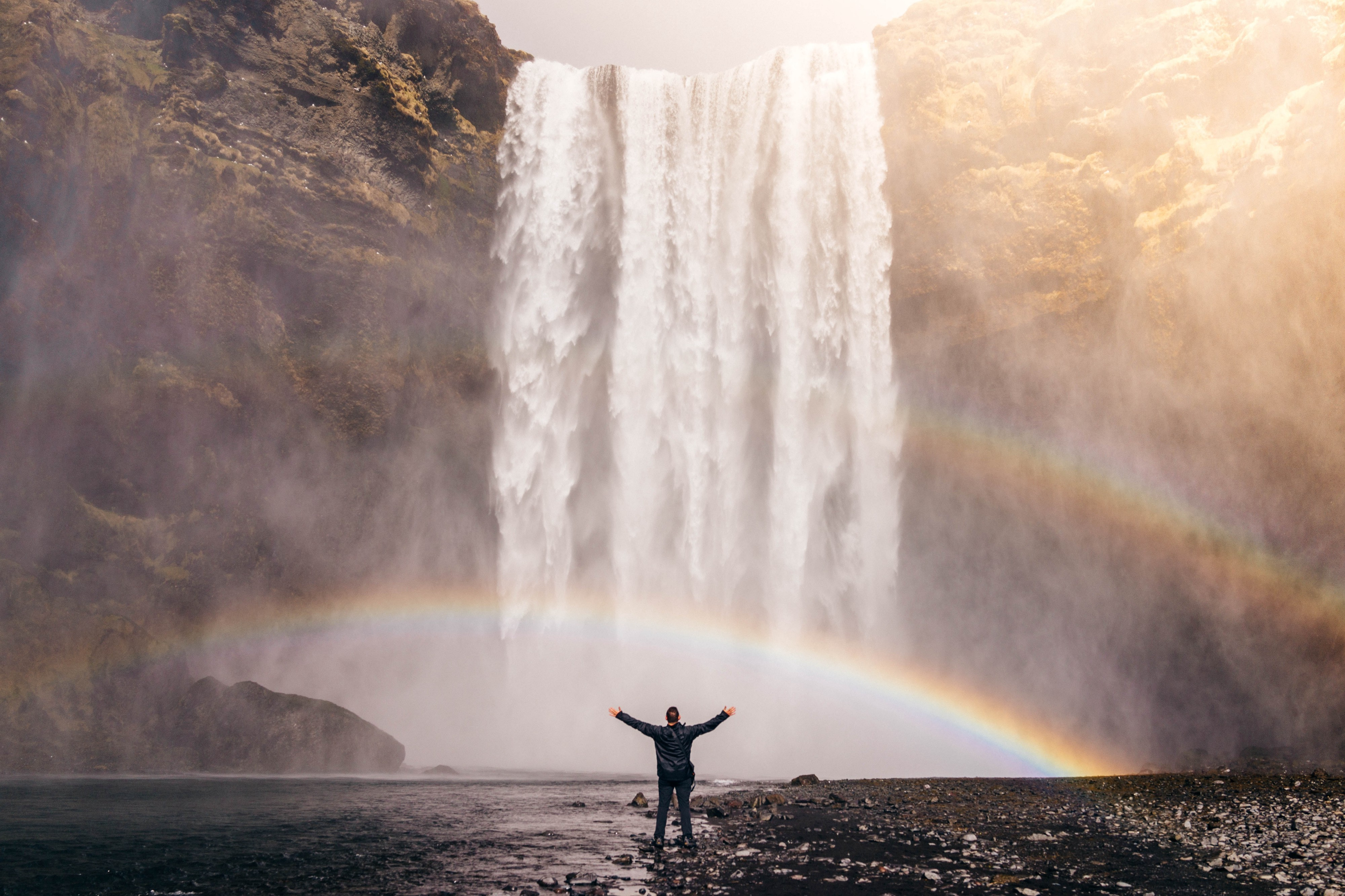 Person standing in awe of a large, beautiful waterfall.