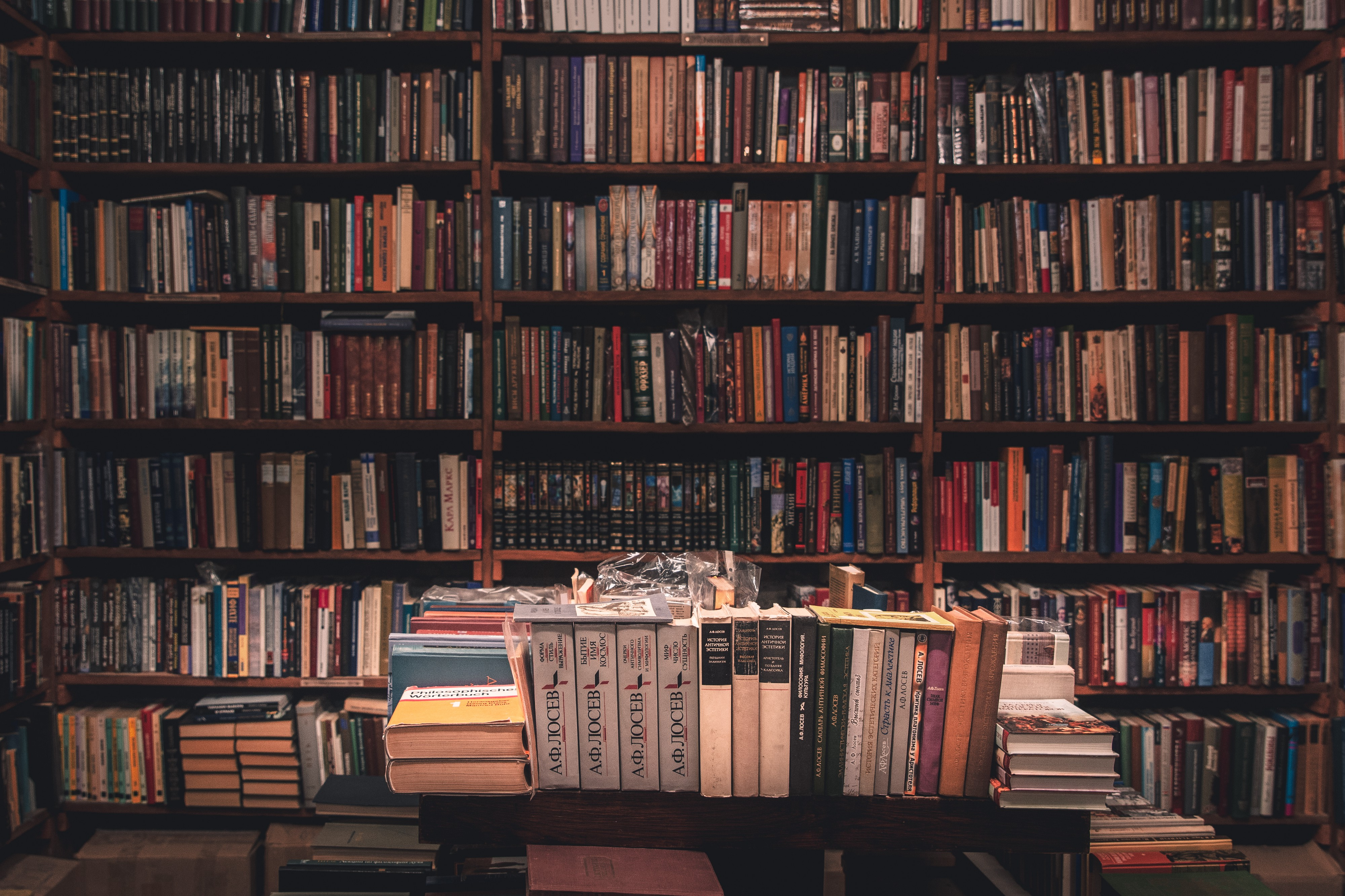 Shelves stuffed with books. Books on a table in the foreground.