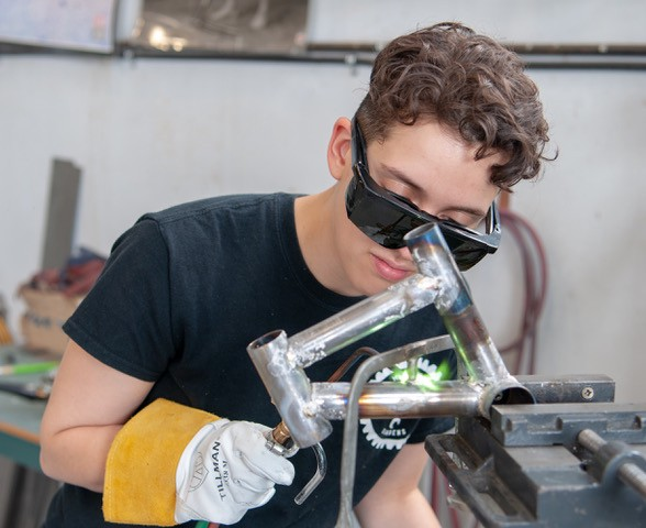 A woman welding a miniature bicycle frame