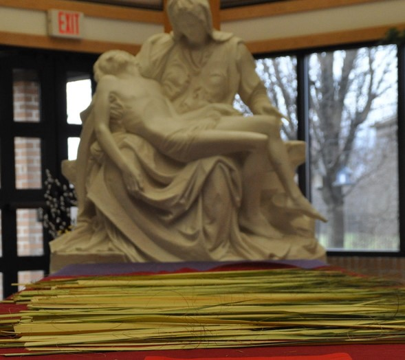 Palm Sunday branches are laid out in front of a statue of the Pieta—Mary holding the limp body of Jesus.
