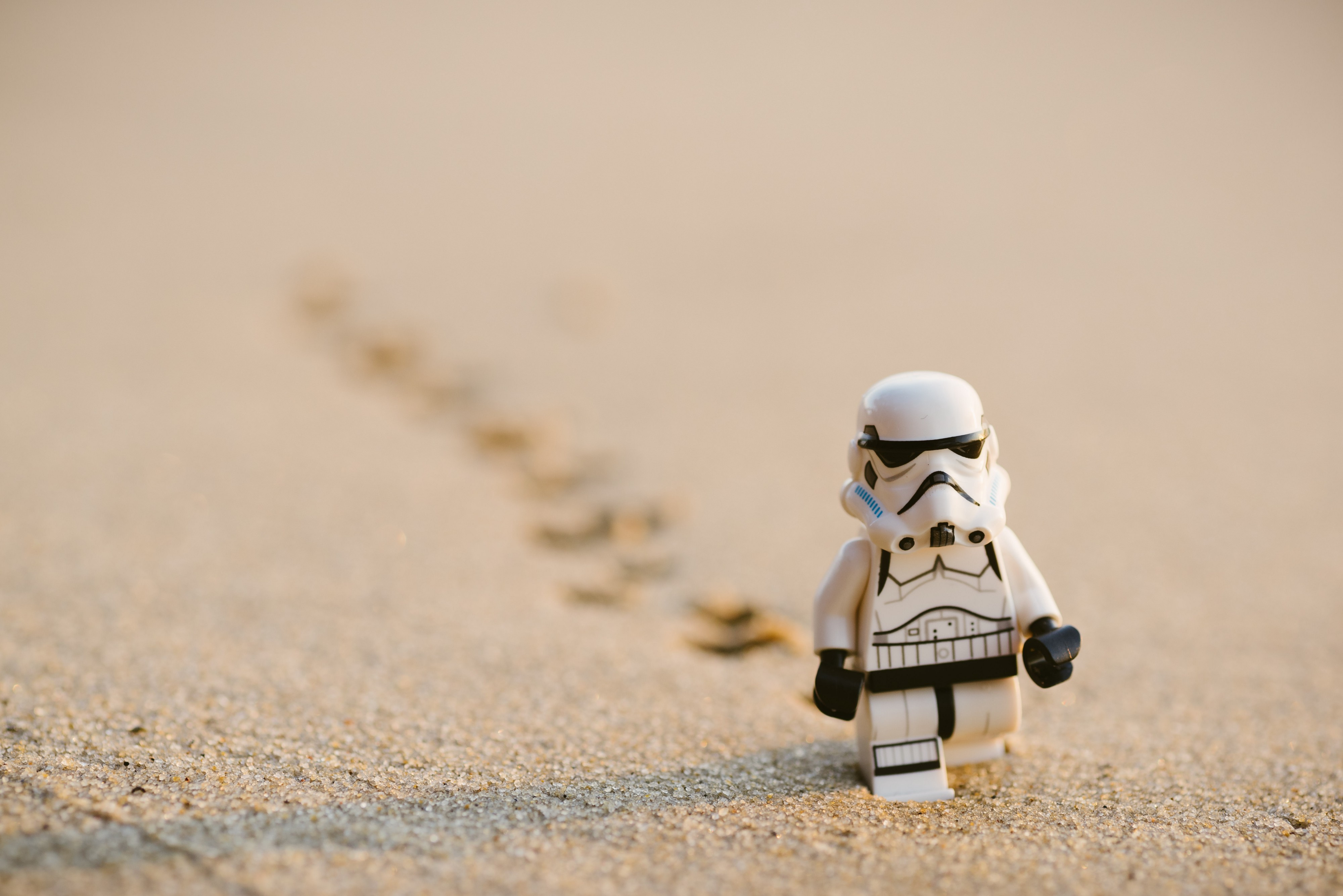 Photo by Daniel Cheung of a Lego Stormtrooper walking through the sand with footsteps behind him.