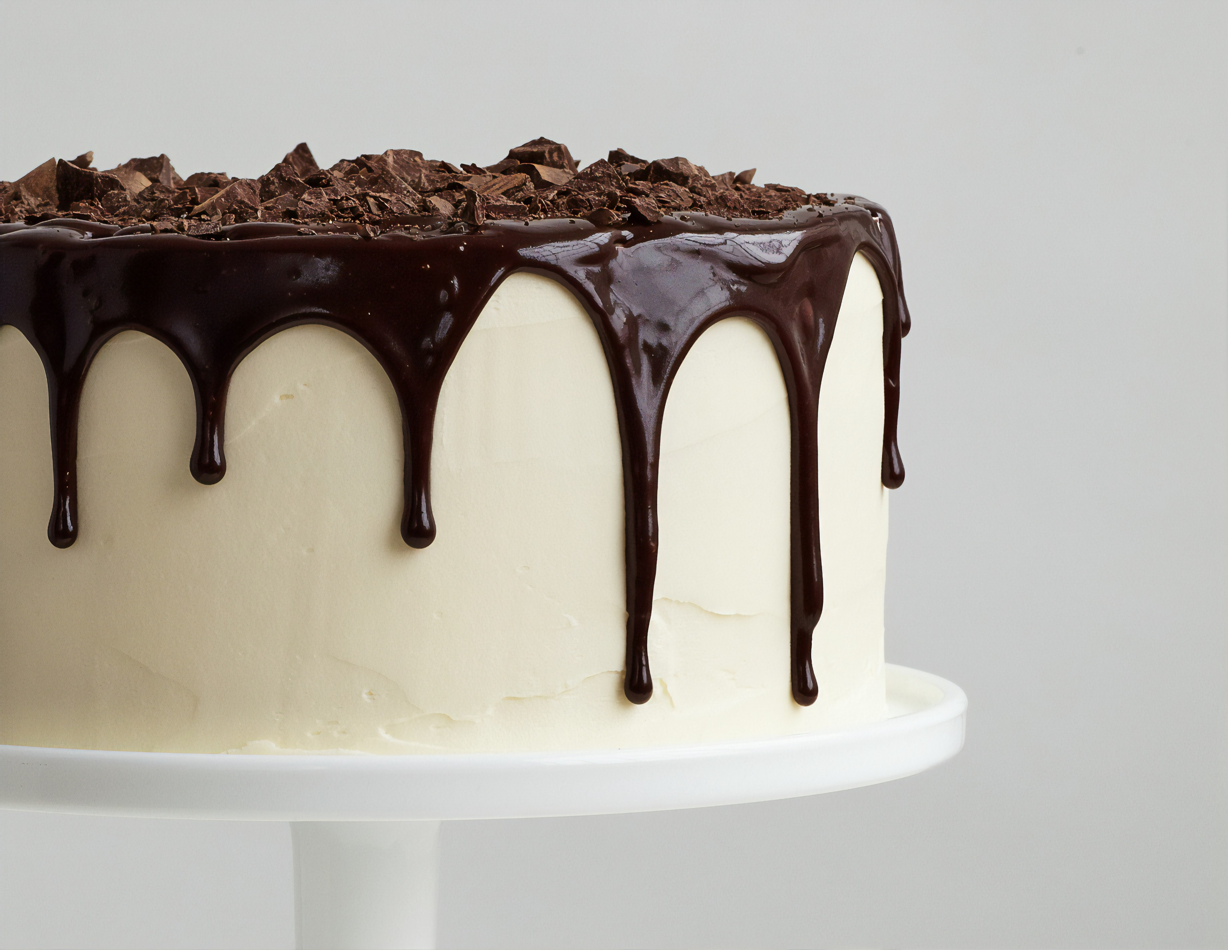 Photo of a vanilla cake on a cake platter with chocolate ganache dripping down the sides and shaved chocolate on top.