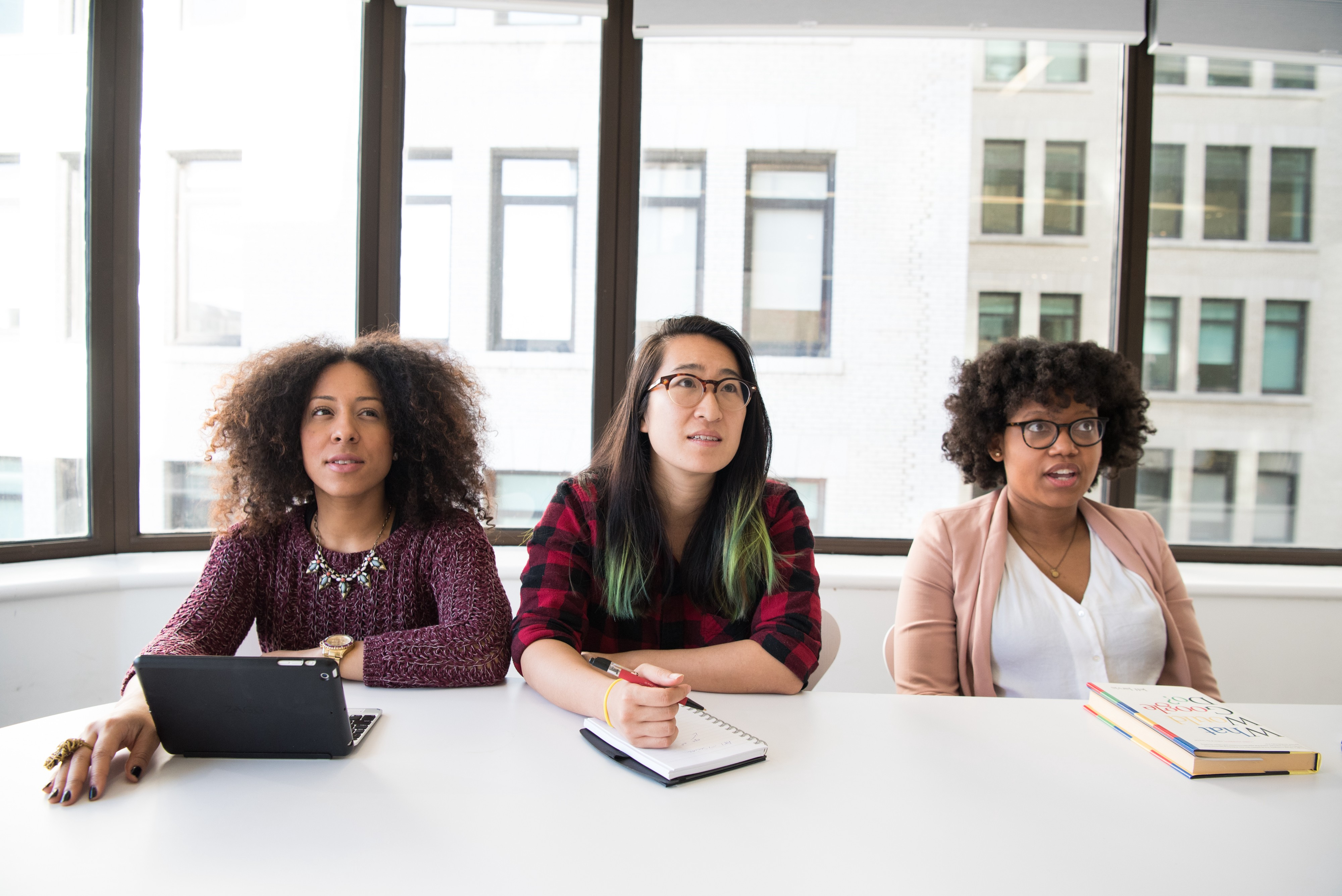 Three woman of color sitting at a table in a windowed conference room, looking surprised and concerned.
