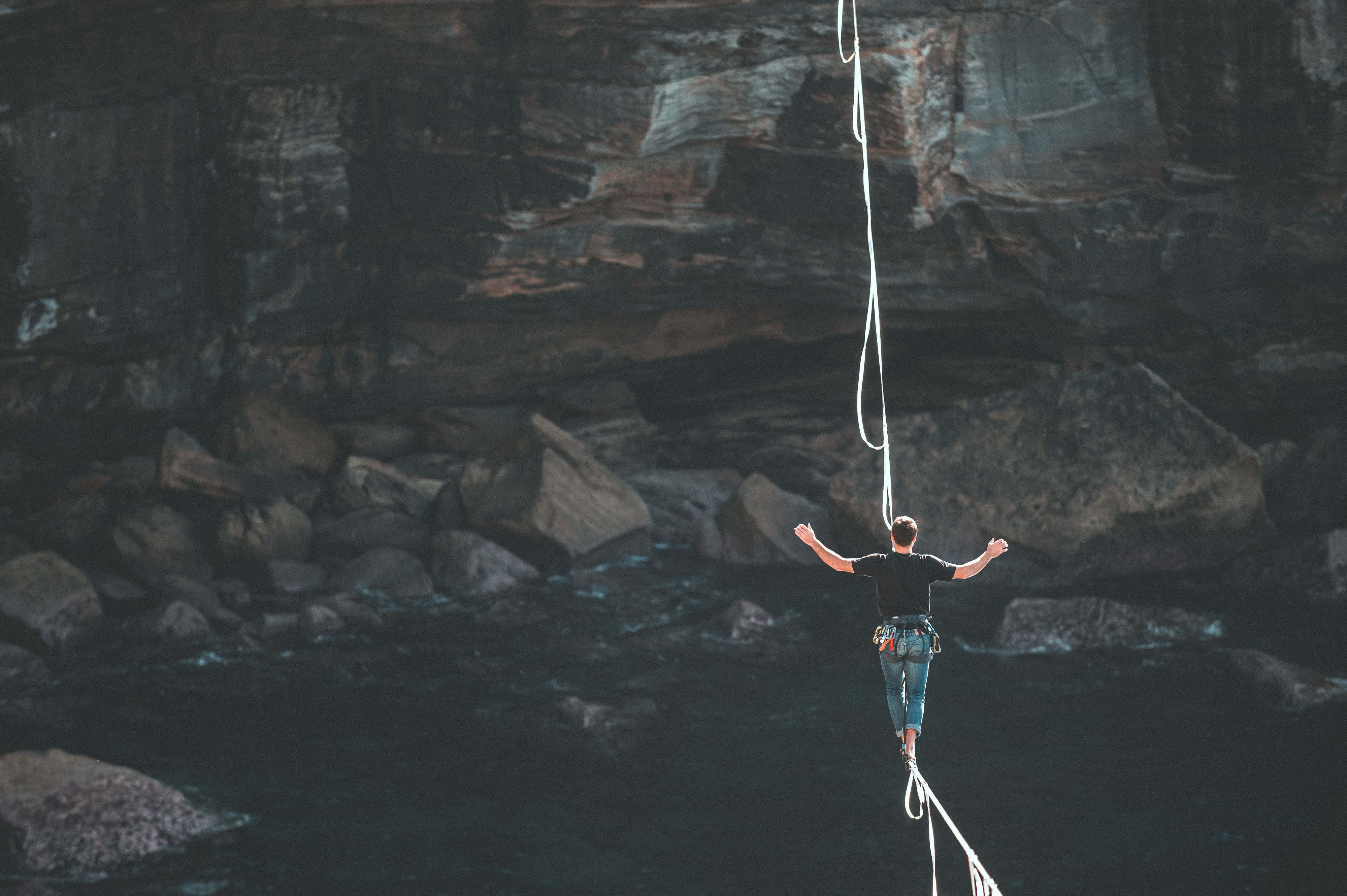 A man walking on a rope at a significant height above water between two mountains
