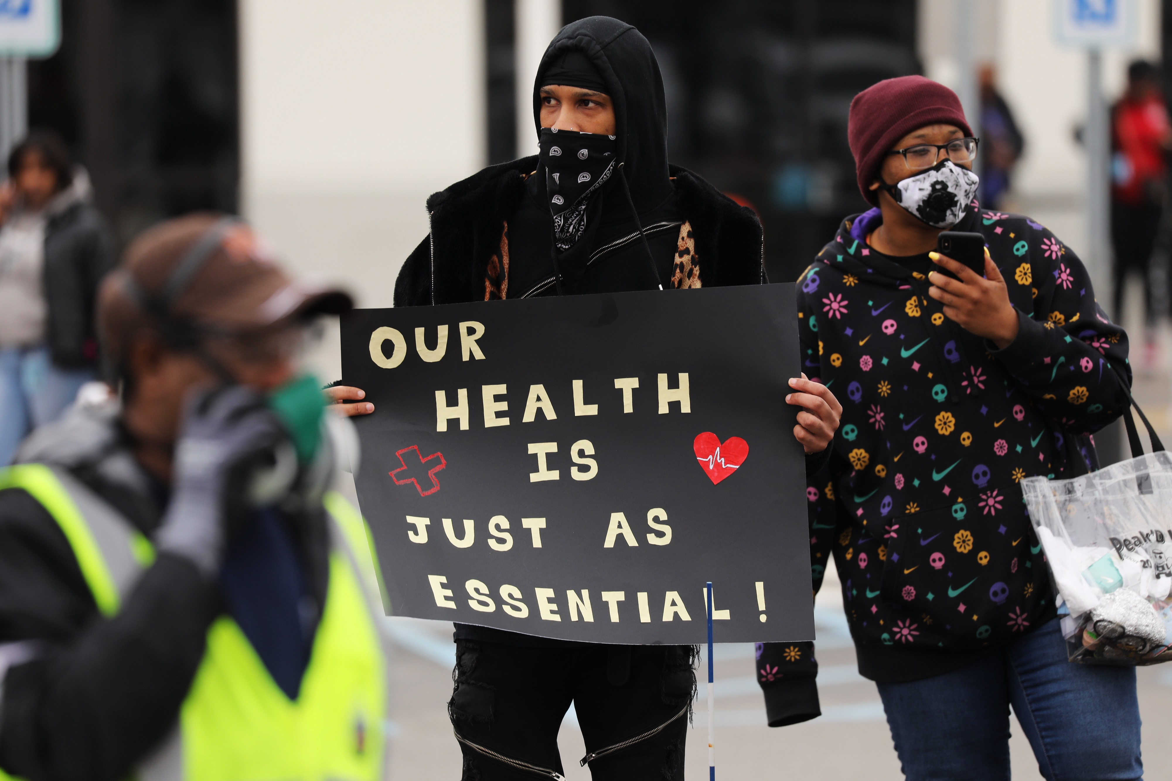 """A photo of Amazon workers protesting. One is holding up a sign that says """"Our health is just as essential."""""""