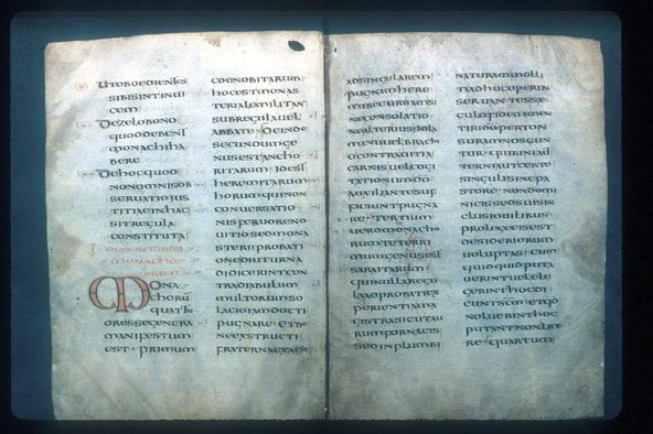 Two facing pages of an ancient manuscript of The Rule of St. Benedict in Latin.