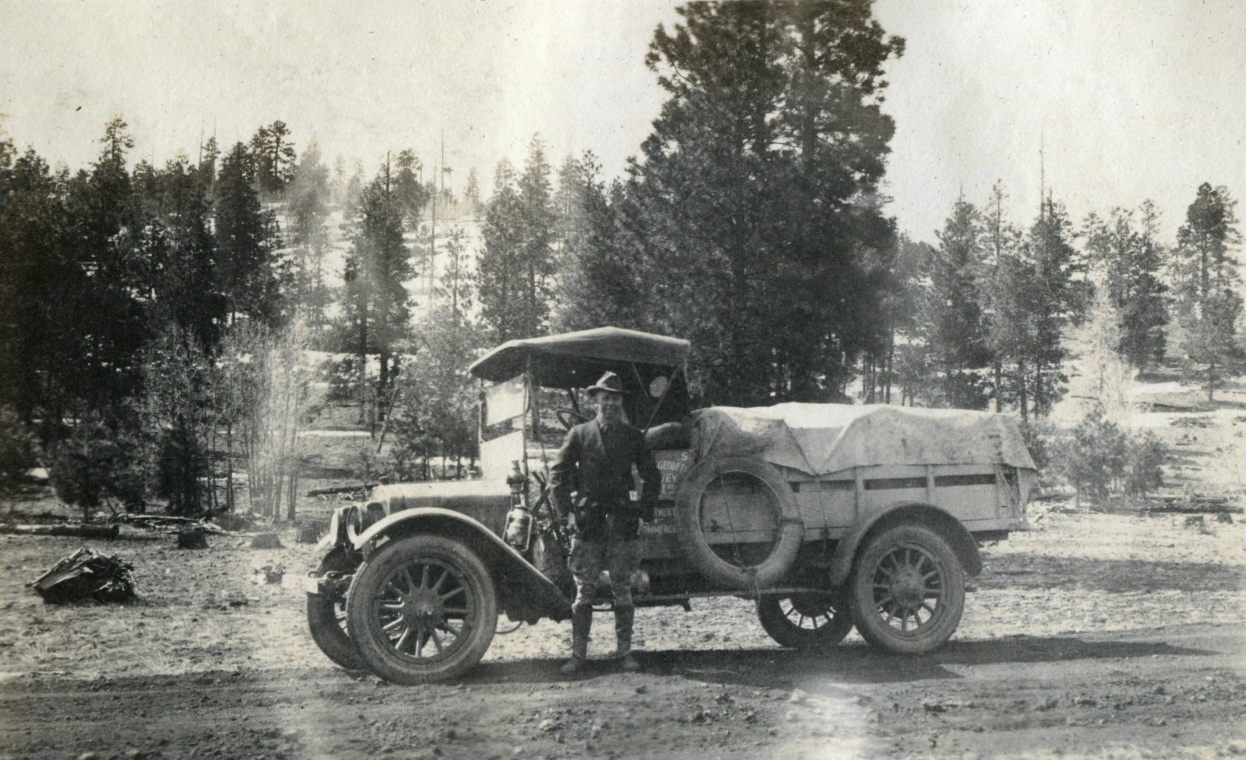 Black and white photo of a man standing in front of a truck.