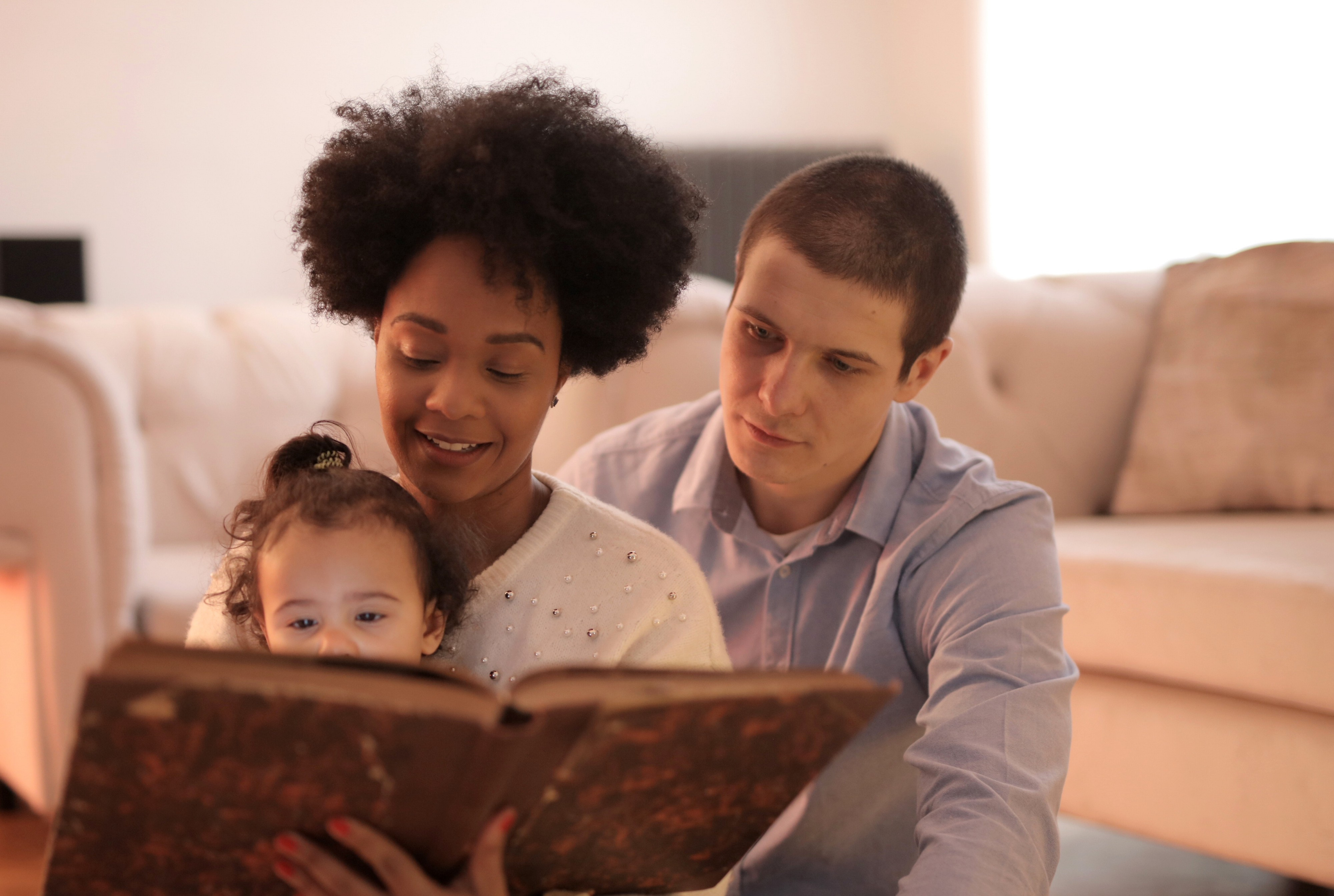 Interracial heterosexual couple of white male and brown-skinned female with short curly hair. The mom is holding a 2 year old on her lap and they're reading her a story from a big, brown, old-looking book. They are sitting on a living room floor next to the couch.