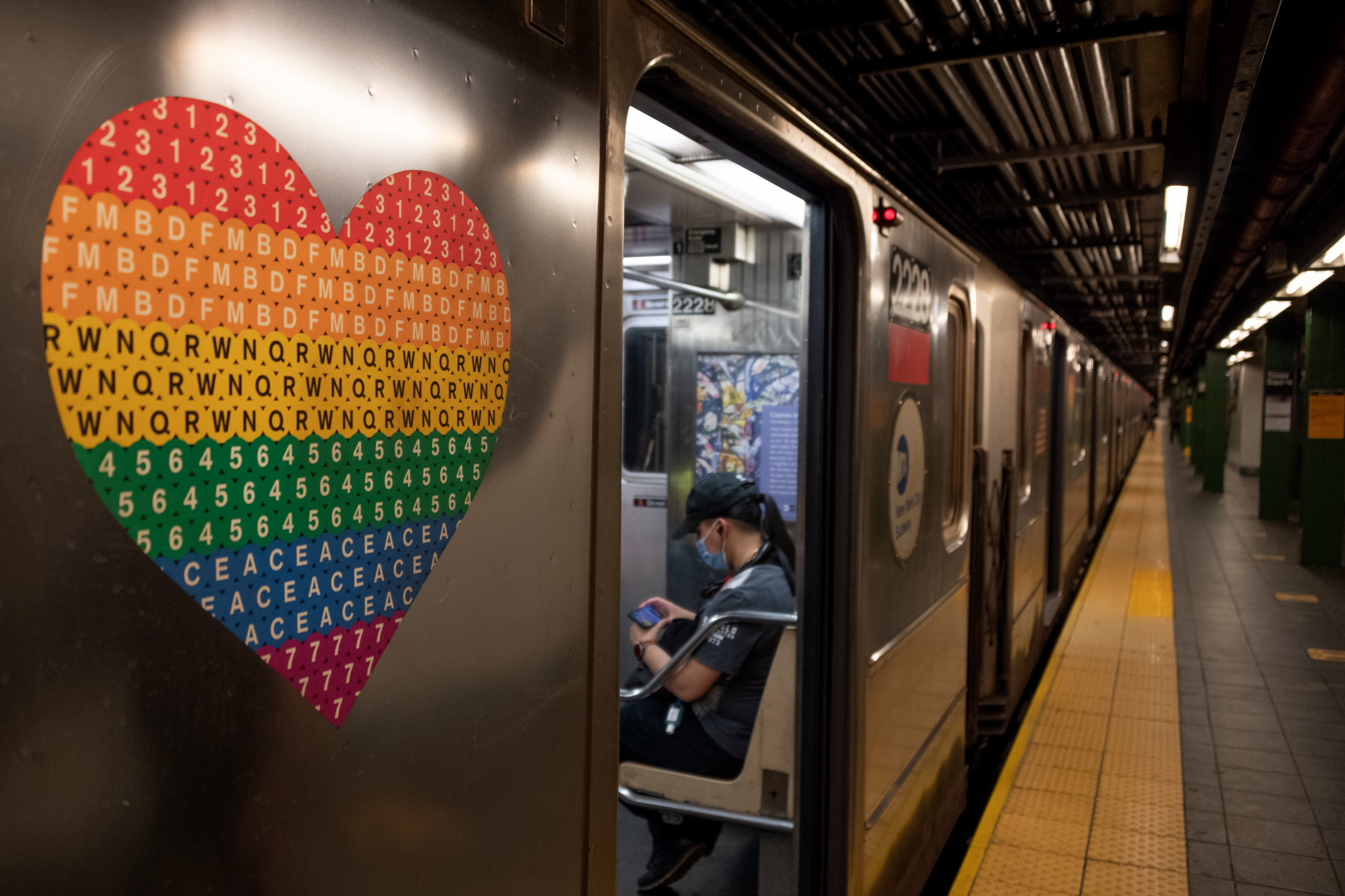 A pride colored heart is seen on a subway car near a person wearing a mask as the city moves into Phase 2 of re-opening following restrictions imposed to curb the coronavirus pandemic on June 25, 2020 in New York City.