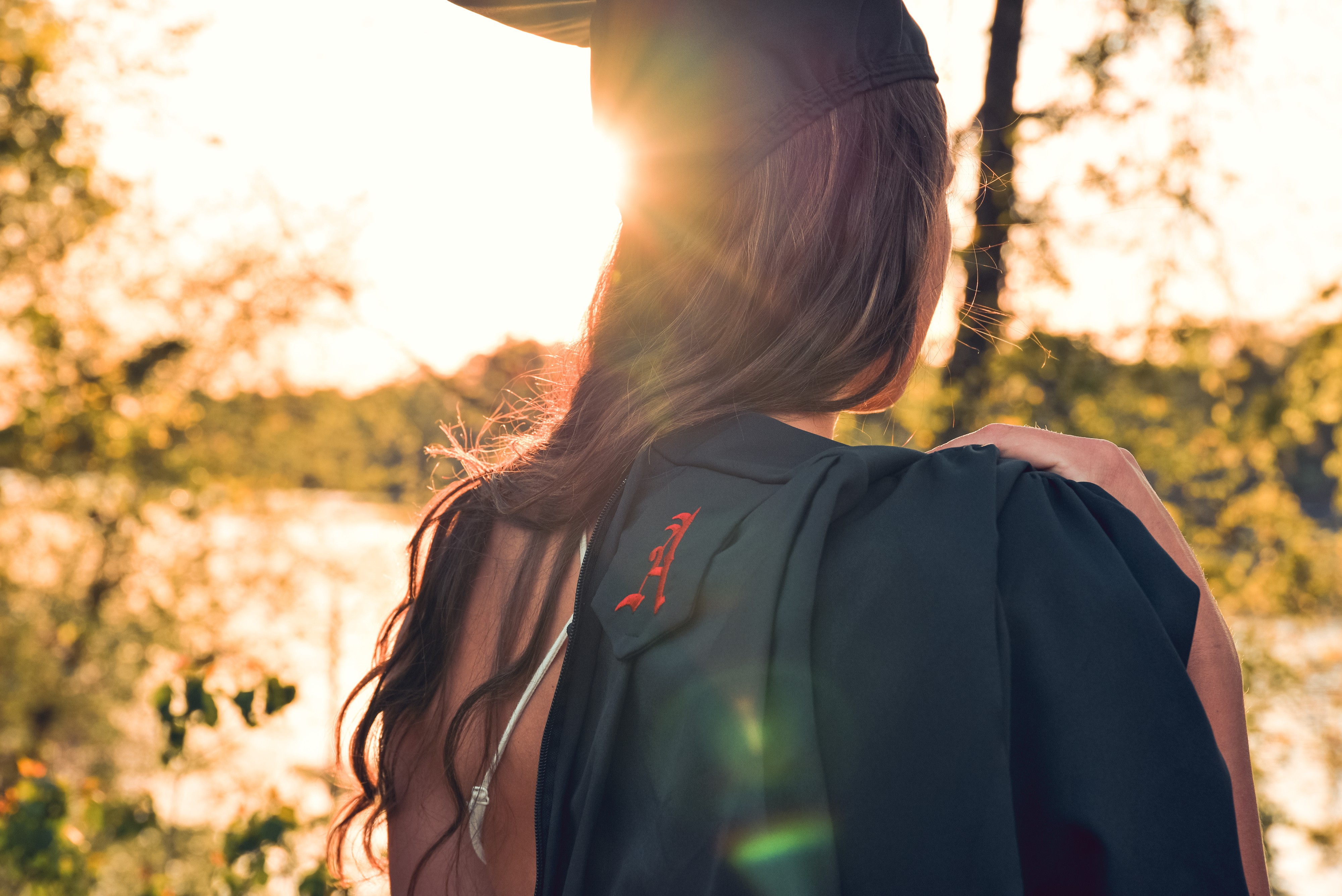 Female with long brown wavy hair outdoors in academic dress and cap.