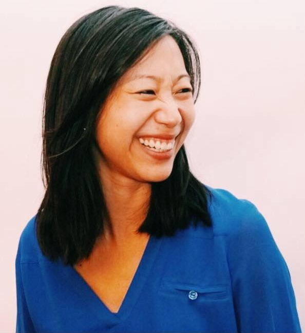 Color photo of Tiffany Yu, an Asian-American woman in a bright blue shirt, looking off to the side and smiling.