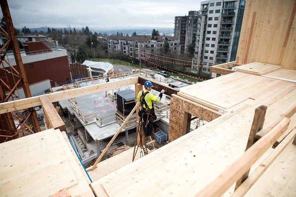 Photograph of a construction worker working on a timber building. In the background there are houses and high-rises.