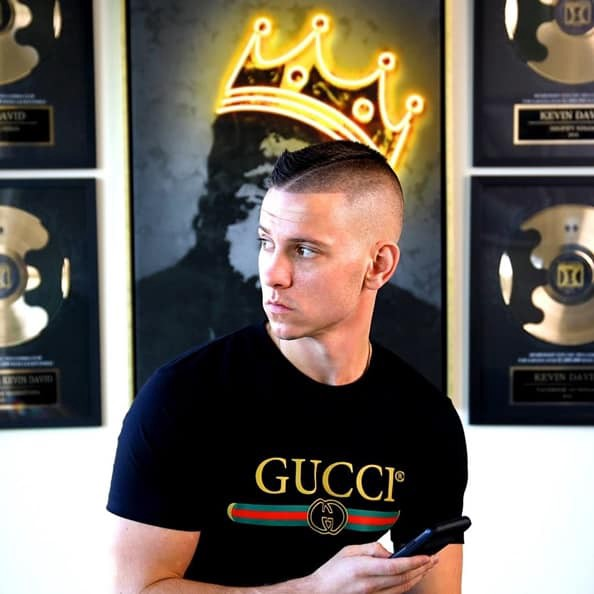 Picture of Kevin David standing in front of a big wall poster and his awards