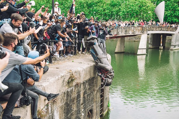 Protestors in Bristol lower a statue into the waters of the dock