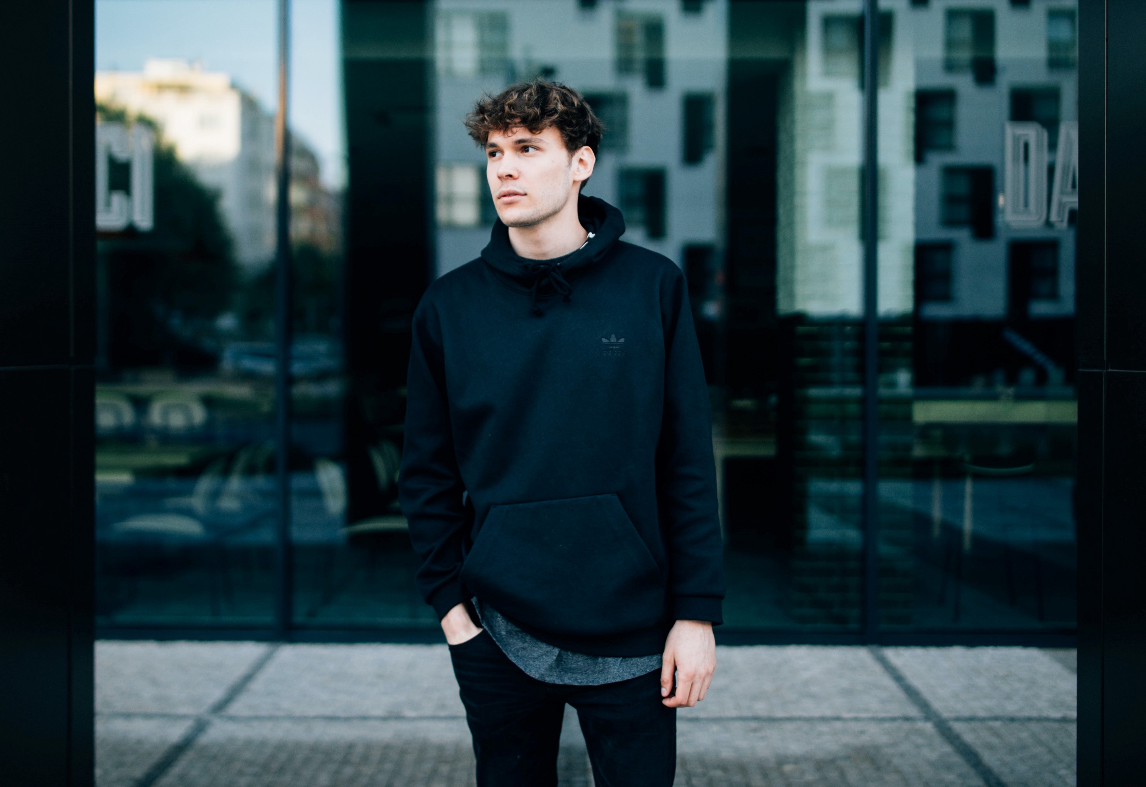 Man with dark curly hair with hand in pocket wearing long sleeve sweater standing on sidewalk with reflection of city behind