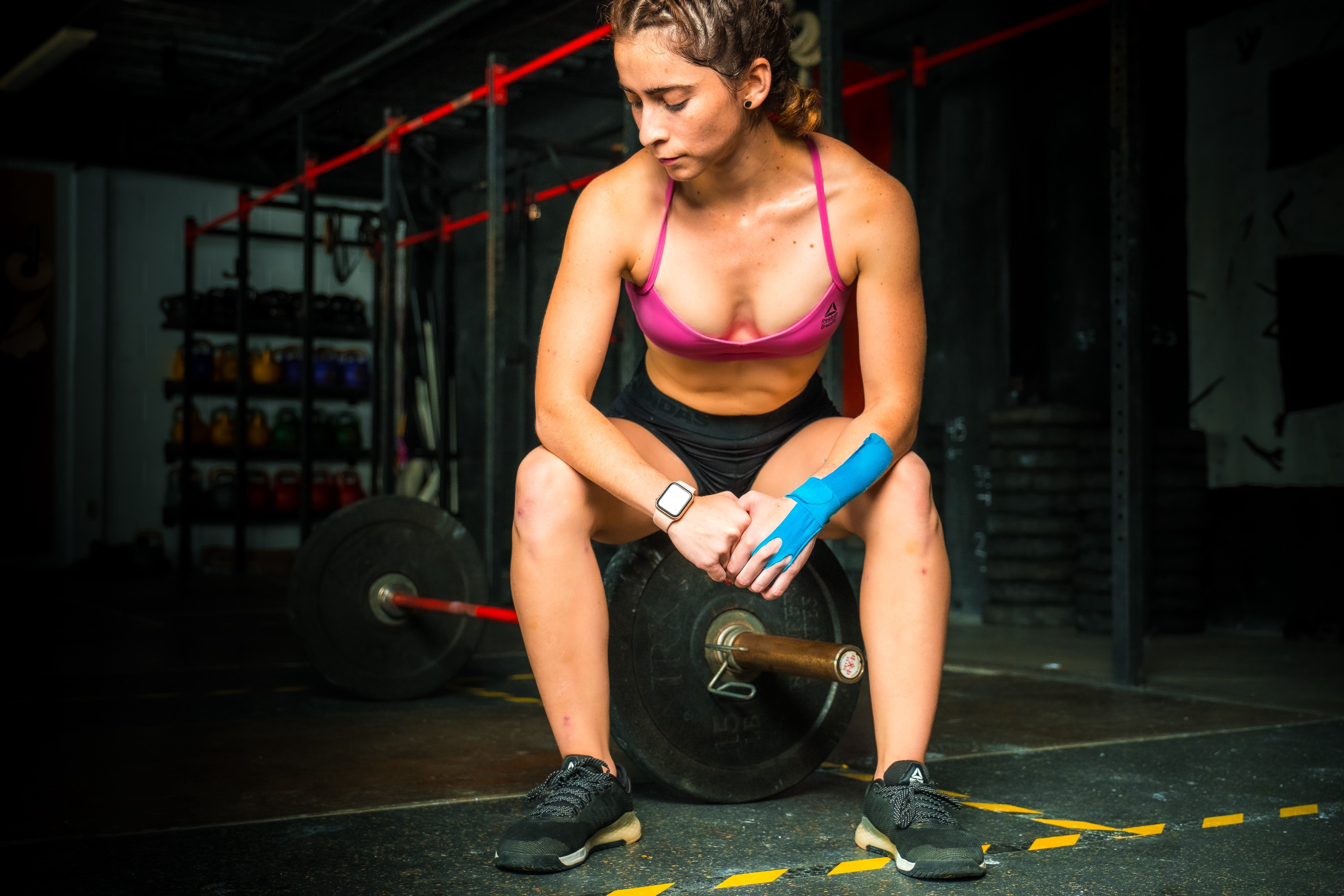 Woman sitting in the gym on a heavy bar. She is wearing a pink bralette and black shorts. She has blue kinesiology tape on her left wrist, and a watch on her right. She is wearing black tennis shoes and has her hair pulled back.