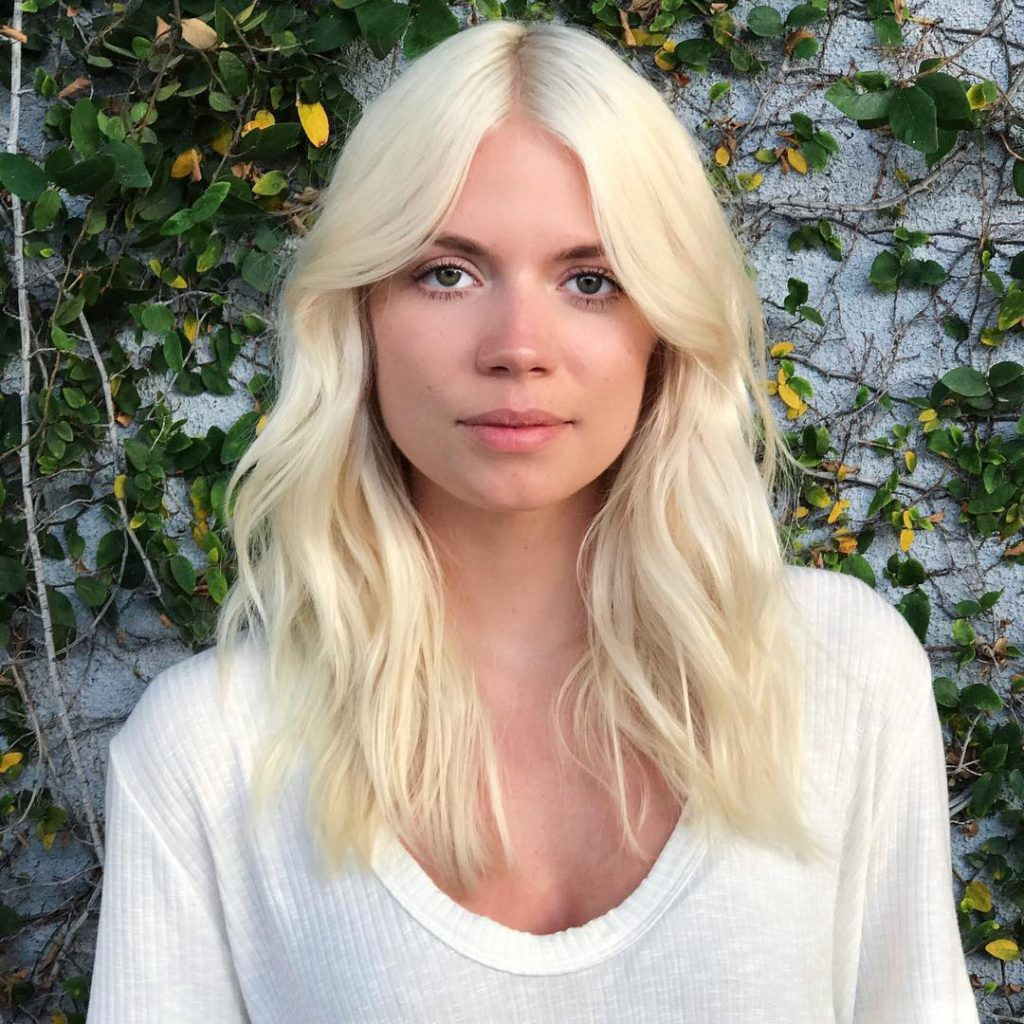 Platinum Blonde Layered Cut With Wavy Texture And Long Curtain Bangs By Hairstyleology Medium