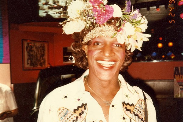 A photo of Marsha P. Johnson in a bar. She is wearing a large headpiece of flowers and smiling hugely at the camera.