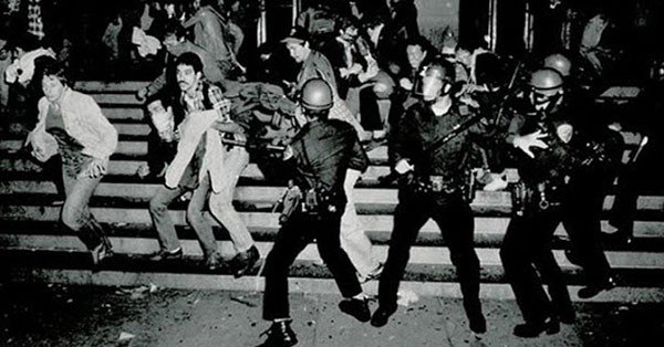 An antique photo of the riots at the Stonewall Inn. It shows police officers in helmets, with batons and full riot gear, chasing after civilians in street clothes, who appear to be running away.