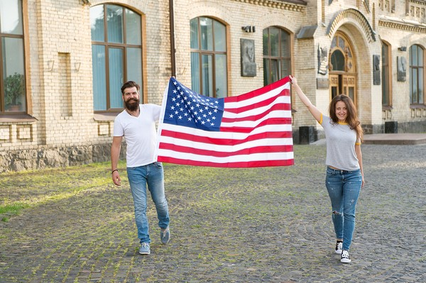 A man and a woman holding an American flag
