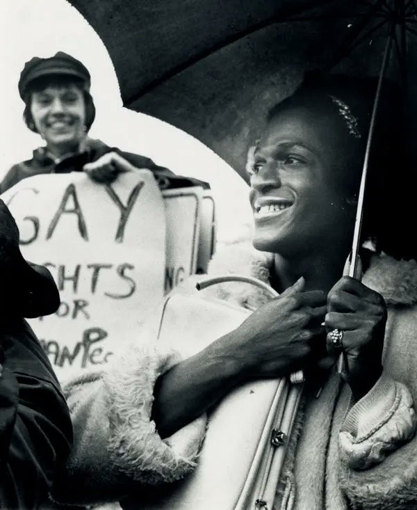 A black and white photo of Marsha P Johnson, holding a black umbrella and a white purse, and wearing a fur coat at a protest. She is smiling.