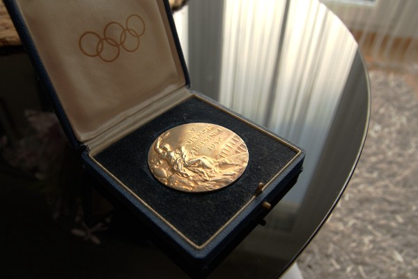Olympic gold medal in box on glass table