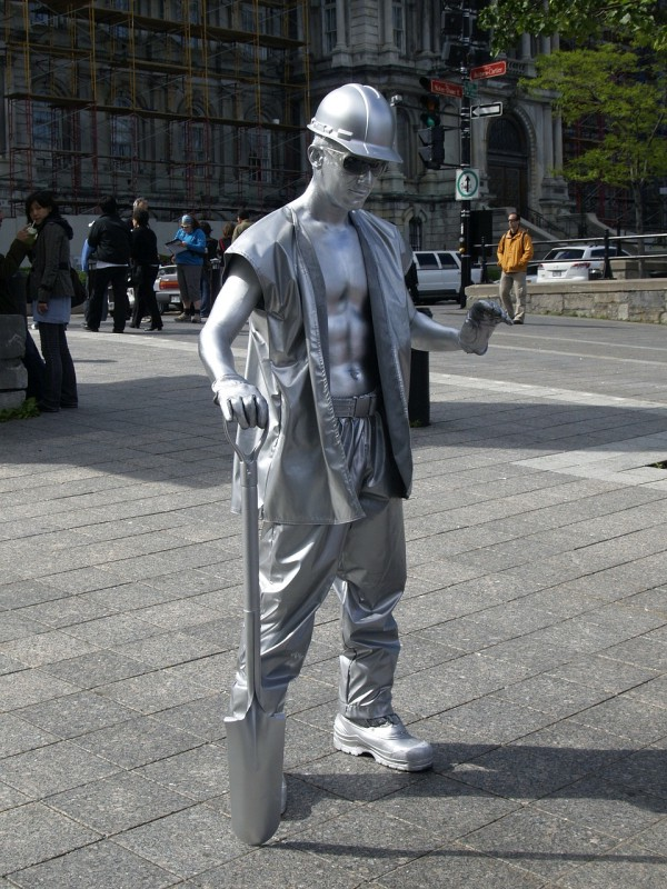 Living statue of a construction worker in shiny silver