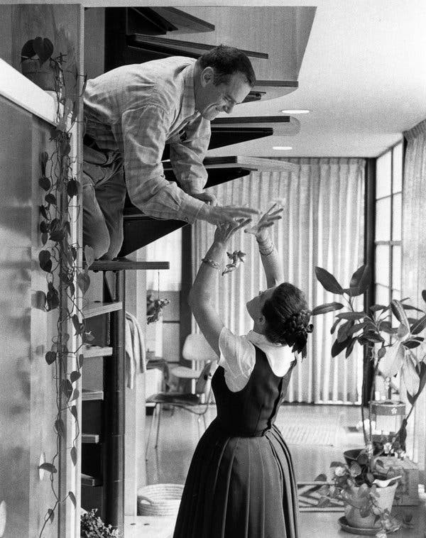Charles and Ray Eames high-fiving in their studio