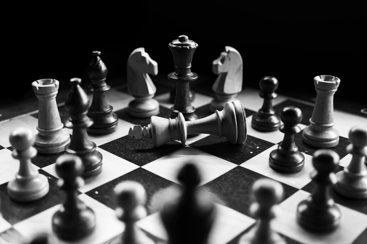black and white image of a chessboard with the king laid down