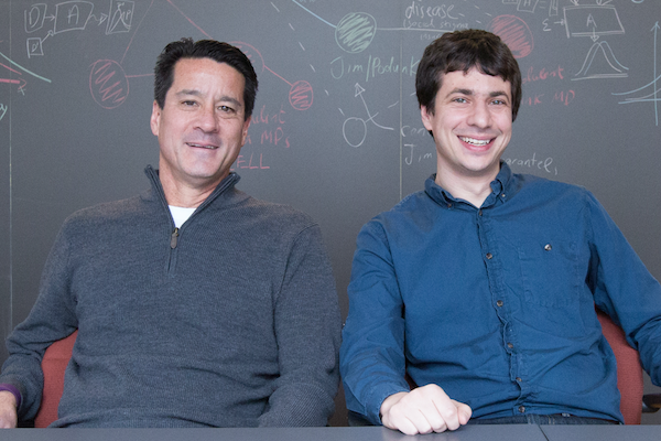 Michael Kearns and Aaron Roth pose in front of an equation-filled chalkboard.