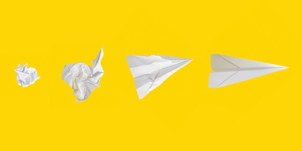 Paper airplanes on a yellow background, from crumpled to well-formed