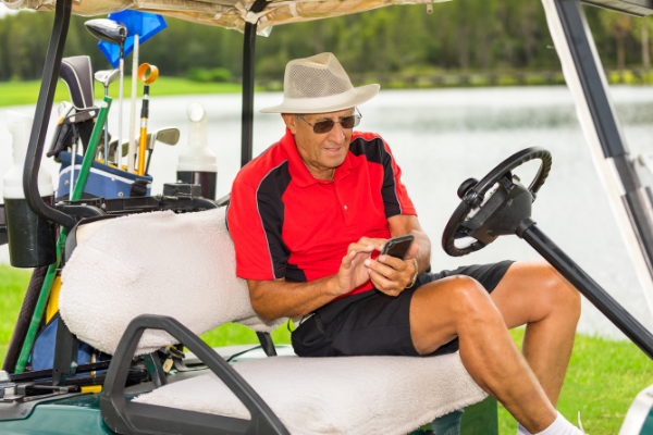 Older gentlemen in red shirt and black shorts in driver's seat of golf court smiling and looking at his phone.