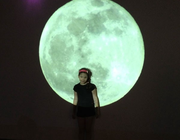 A little girl with a huge moon image at the background