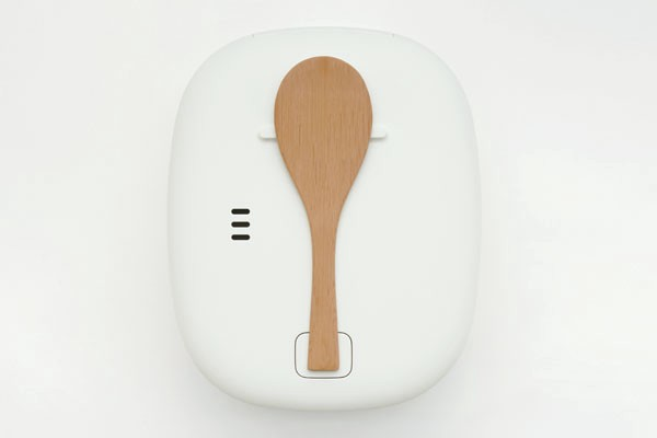 A photo of the white Muji rice cooker from above on a white countertop. The bamboo spoon is centered on the lid.